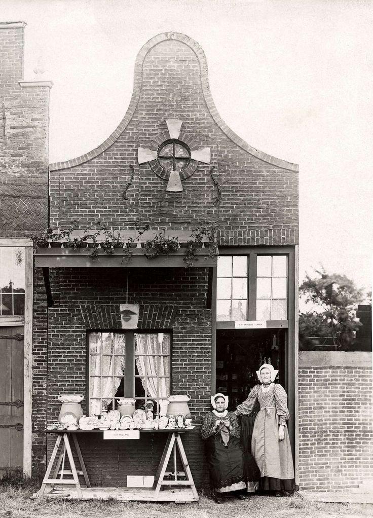 Steden en dorpen. Feestelijkheden in Laren(N-H). In het dorp is een decor van historische huizen opgebouwd. Voorbeeld van een zilver-en aardewerkwinkeltje met daarvoor de verkoopsters. Laren 1914 #Laren #Gooi #NoordHolland #vierkant