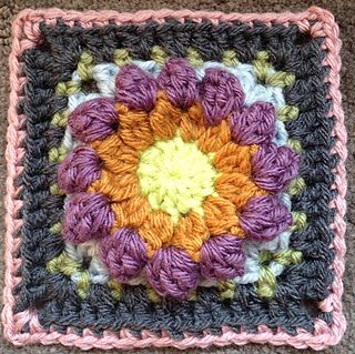 """A beautiful floral 6"""" crochet square where the flower stands proud of the background."""