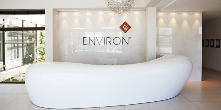 Environ Skin Care reception area features a curved reception desk that mirrors the curve of a woman's body and framed with a sheer wall of polished marble behind it, bearing Environ's corporate identity. | interior design by Haldane Martin | photography by Micky Hoyle