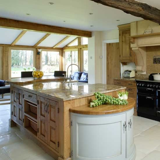 Kitchen extension with wood kitchen island, granite worktop, black range cooker and wood cabinetry
