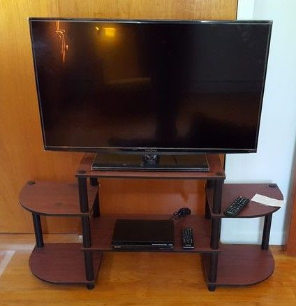 """Insignia 39"""" flat screen TV, Sony disc player, modern TV stand, remotes."""