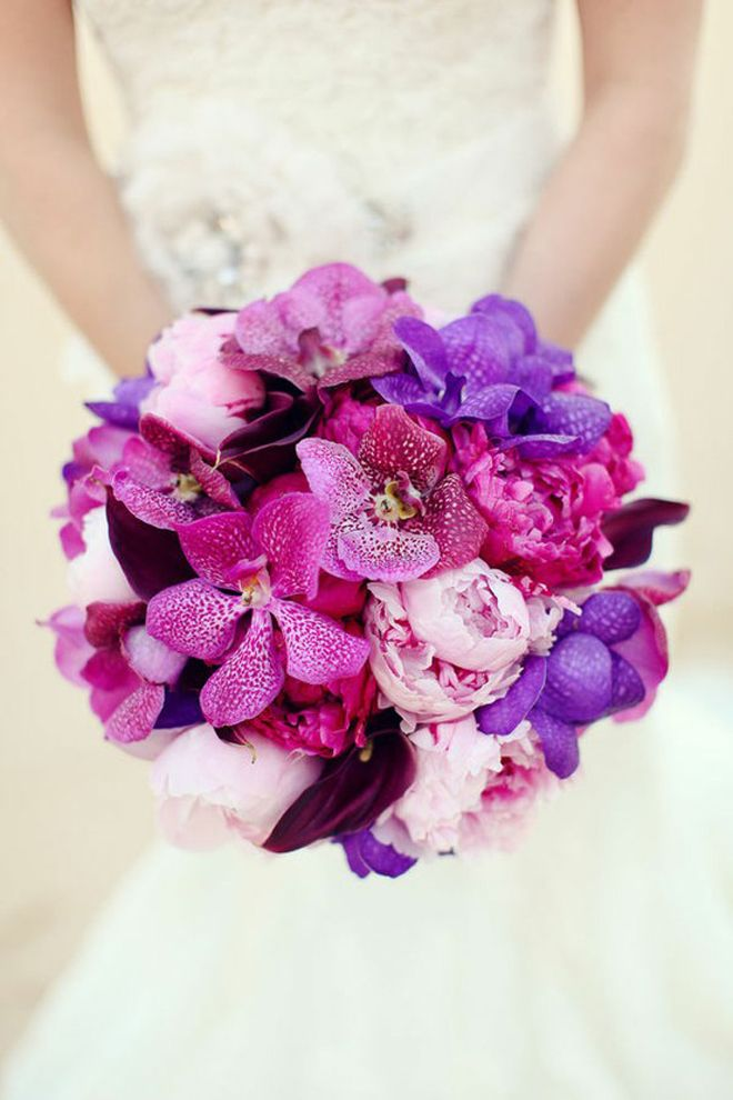 Vanda and mokara orchids are stunningly paired with blush and fuchsia peonies and dark callas.