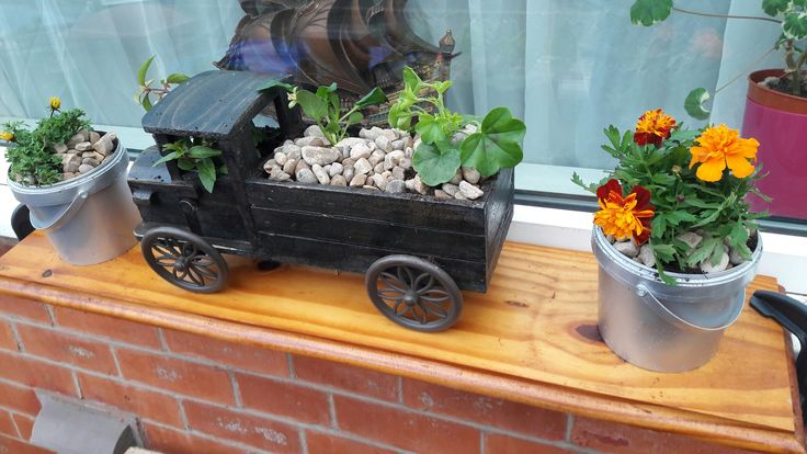 Repurposed shelf + ornament + upcycled yoghurt buckets + plants = new front yard feature!