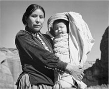 Black and white photograph of a Native American woman holding a child