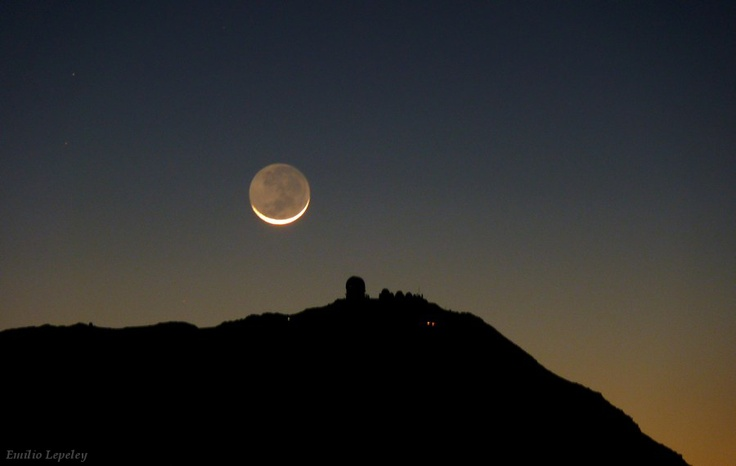 A thin crescent moon sets over Cerro Tololo Observatory. The Cerro Tololo Inter-American Observatory is a complex of astronomical telescopes and instruments located at 30.169 S, 70.804 W, approximately 80 km to the East of La Serena, Chile at an altitude of 2200 meters.