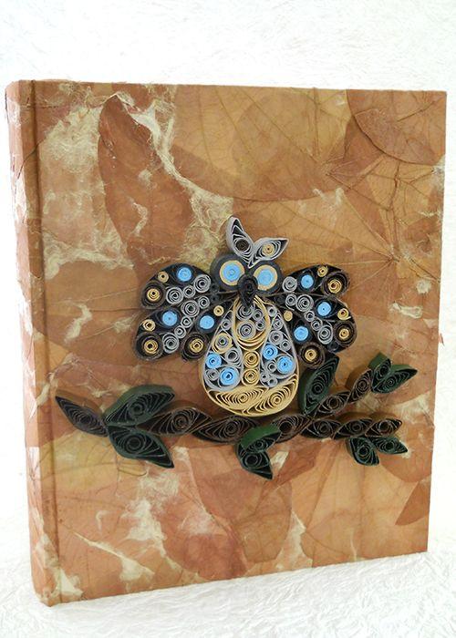 Album portafoto, con carta che presenta delle foglie come inserti, ed un gufo realizzato a mano con la tecnica del quilling
