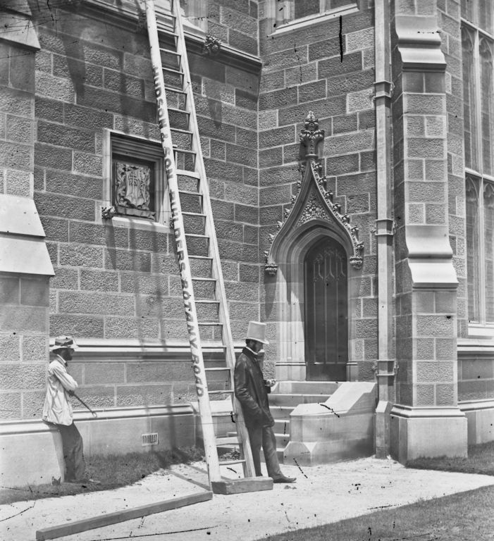 Meet the photographer: Professor John Smith timing an exposure while leaning against a ladder (Hudson and Son -  builder), north doorway from Science Road, Sydney University