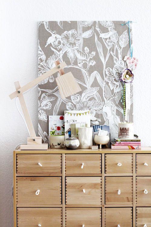 une planche recouverte de tissu agrafé au dos: donne de l'unité au petit bazar devant et de la hauteur au meuble sur lequel elle est posée…  (via decor8» Blog Archive» Corners of My Home)