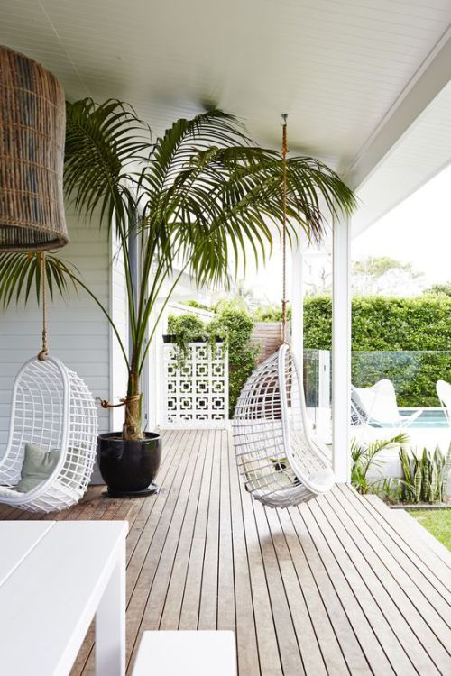 Tropical inspired outdoor patio space with fun hanging seats