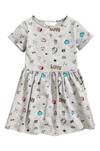 Een jurk van lichte joggingstof met een print en een licht geruwde binnenkant. De jurk heeft korte mouwen met een vastgestikte omslag, een naad in de taille