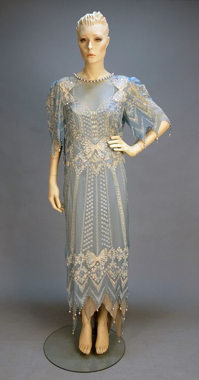 "ZANDRA RHODES HAND PRINTED CHIFFON GOWN, c. 1980. Pale blue with low cowl back, handkerchief pointed short sleeve and hem edged in pearl beads, white printed bow design having rhinestones and sequins at shoulder and back, jersey under dress. Label ""Zandra Rhodes London"". B-36, L-58. (Under dress slight stain, small splits near back hem, missing one pearl) dress excellent. $390."