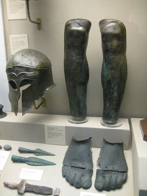 Greek Corinthian helmet, greaves, foot armour, the javelin tips and part of a sword or dagger.