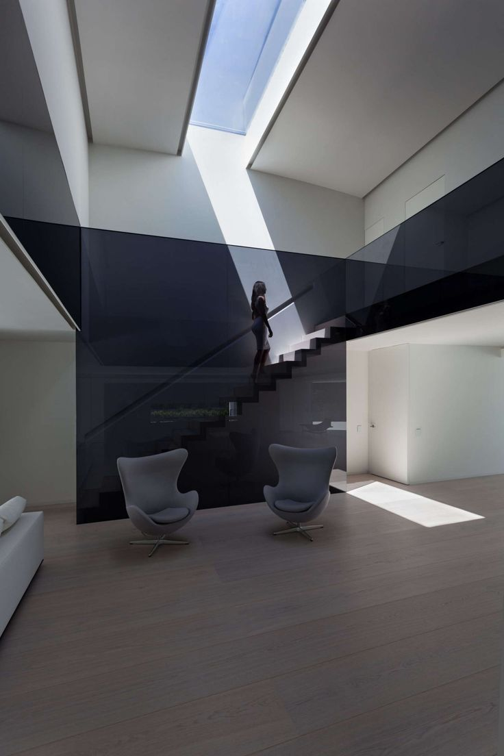 http://boomzer.com/golf-course-sight-or-a-obvious-exterior-make-for-a-contemporary-marvel/gray-arm-chairs-grey-sofa-egg-wooden-floor-black-wall-glass-staircase-ceiling-glass-tile-fran-silvestre-arquitectos/