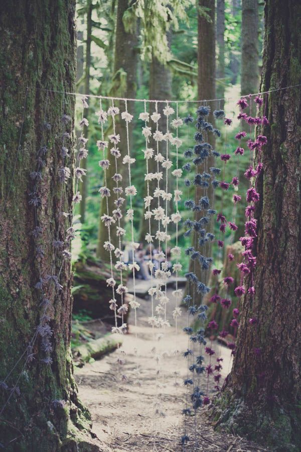 These yarn pom poms give the forest a little color and add a whimsical touch to the wedding |  Photo by Terra Lange Photography via june.bg/1qKHSED