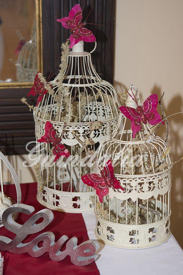 """Detalle de la mesa con jaulas decoradas con mariposas en los mismo tonos granate y letras """"Love"""" en plata."""