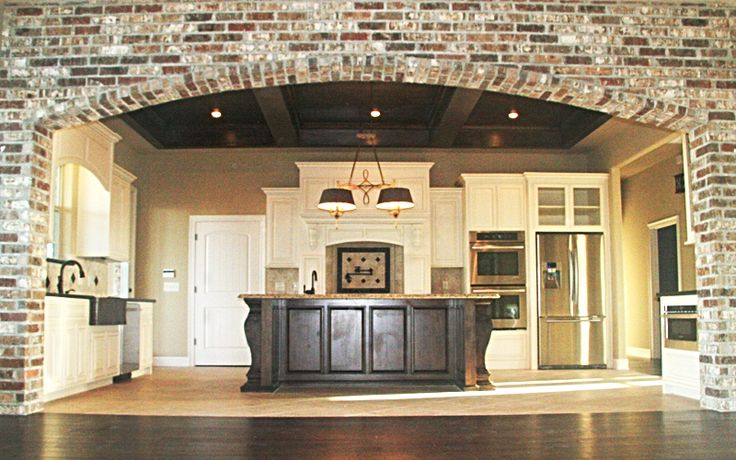 The Acadian Dream Home Gallery open to kitchen through widened arch :) I love all the white with the contrasting dark island. It's a very natural-looking kitchen but I hate the light fixture! At least it's an easy fix.