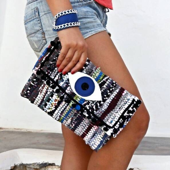 "Whimsical and fun, this kilim clutch decorated with the evil eye and colorful pom poms is sure to attract attention. Decorated with colorful pom poms its a statement piece that will carry your essentials in style. Pair it with a simple tee or your favorite maxi dress for easy going boho flair. Each bag is made of a kourelou a small rug made of recycled strips of cotton jersey fabrics. This makes every piece unique as no two bags are completely identical. Size: 11""x8,5"", flap 4""/28x21cm,..."