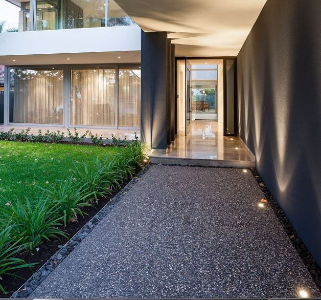 Pathway to front door. Polished concrete/aggregate at front door. uplights on side