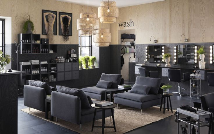 A hair saloon in dark grey and natural colours furnished with wall cabinets for displaying shampoos and a waiting area with comfortable armchairs.
