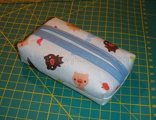 So geht's: Schnelle Taschentüchertasche  Für Karo ;)    Das braucht man:    Stoff, Bügeleinlage, Schrägband    Stoff zuschneiden:    Das Stoffstück sollte die Maße 17-18 cm x 15 cm haben.    Gleich großes Stück Vlieseline aufbügeln:      Kanten Versäubern:    Am schnellsten mit der Overlock. ;)    An die kurze Seite kommt Schrägband:      Ich nähe es mit dem wunderbaren Schrägbandfuß an:      Die Seiten mit dem Schrägband nach innen rechts auf rechts klappen:    Ich fixiere immer mit Nadeln.