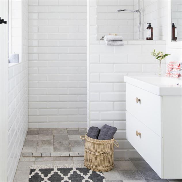 På samma plats som det gamla badrummet i rosa, men i helt ny kostym. Klinkers Biarritz cendre i skiftande grå nyanser. Väggkakel Fasad blank vit. Vit badrumsinredning från Ikea med knopphandtag i trä från H&M home.