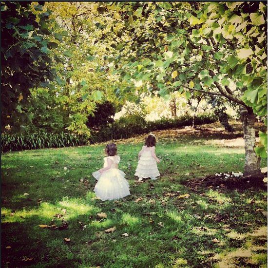 Flower girls exploring at a garden wedding.
