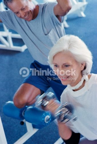 Stock Photo : Senior couple exercising in a health club