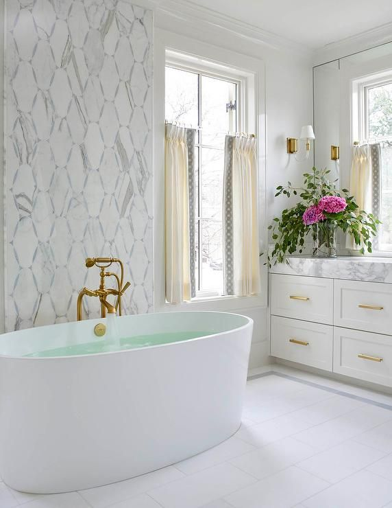 a mosaic marble accent wall stands behind an antique brass vintage bathtub filler and an oval bathroom remodelingbathrooms