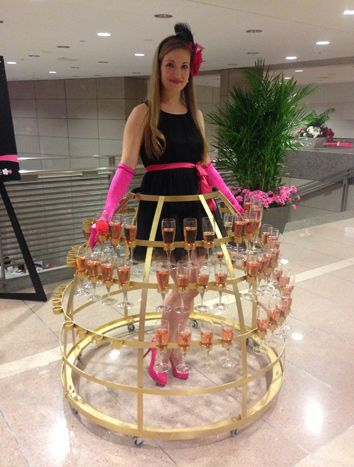 A model wearing a skirt of pink champagne flutes welcomed guests to the Pink Tie Party on Thursday. Photo: D. Channing Muller for BizBash