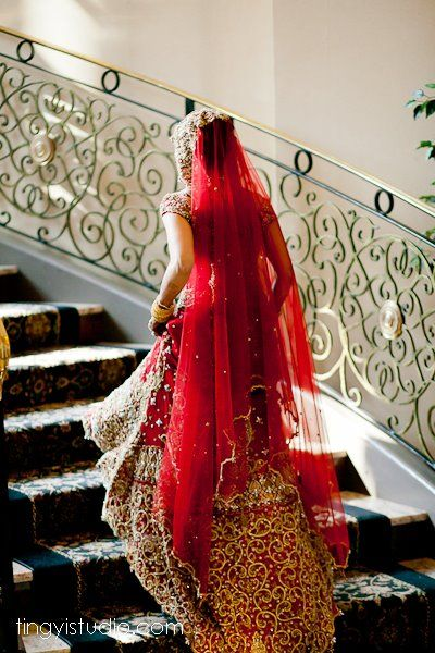 Beautiful Indian bride climbing stairs in red lengha