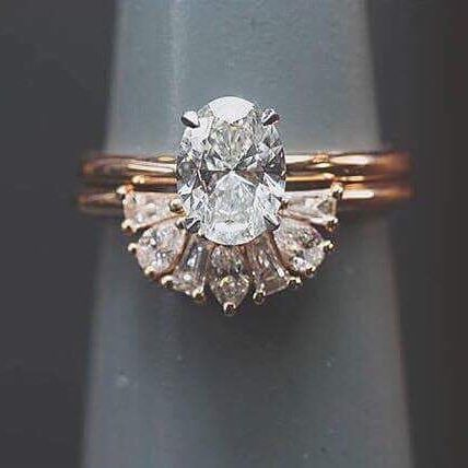 oval cut diamond in yellow gold band with unique wedding band