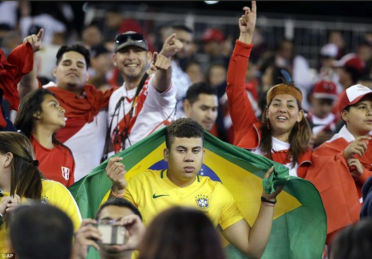 A Brazil supporter looks far from happy during the Copa America clash in Foxborough, Massachusetts as he is surrounded by Peru fans