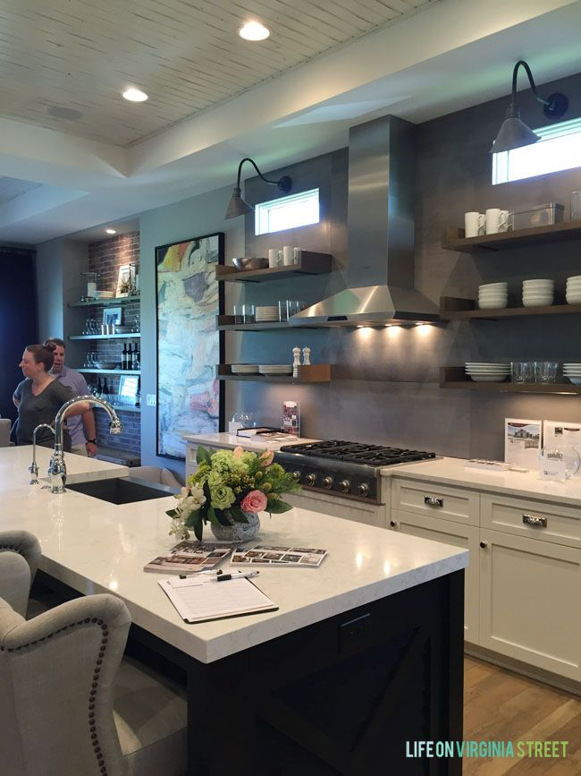 Urban and industrial style kitchen with open shelving, white cabinets, black island and warm touches throughout via Omaha Street of Dreams Kitchen - Life On Virginia Street