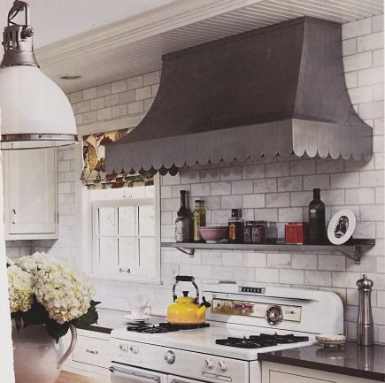 scalloped range hood and subway tile