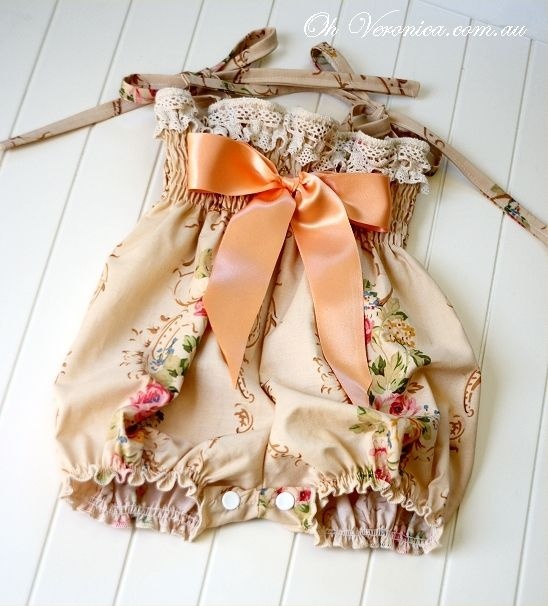 LUXE RARE Paris Playsuit!Re-released as a small amount of this rare very out of print designer cotton is again on offer.The prettiest playsuit ever!Crotch studs for nappy changing. The bodice is shaped to mimic vintage smocking. Shoulder ties, contrasting polka dot back and dainty ribbon bow.(All lace trims will vary from playsuit to playsuit as they are all unique and handmade. Vintage embroidered wedding lace will feature on the bodice).SIZES
