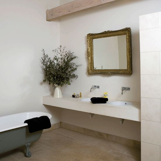 An antique mirror and a classic roll-top bath are combined with a sleek concrete shelf that holds the contemporary basins and taps, while a limestone floor creates a neutral base for the room.