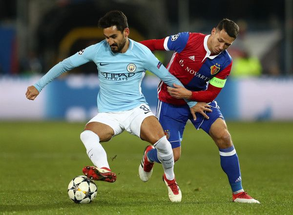 Ilkay Gundogan Photos - Ilkay Gundogan of Manchester City is challenged by Marek Suchy of FC Basel during the UEFA Champions League Round of 16 First Leg  match between FC Basel and Manchester City at St. Jakob-Park on February 13, 2018 in Basel, Switzerland. - FC Basel v Manchester City - UEFA Champions League Round of 16: First Leg