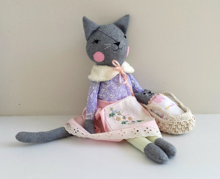 This one of a kind, handmade cat doll is named Elsa and she has a kitten that likes to sleep in her Moses basket.This is my first doll to be stuffed with 1005 pure New Zealand wool stuffing.Elsa measures approximately 46 cm (18 inches) tall from tip of her ears to toes.She wears a removable skirt and reversible wrap with ribbon ties at the front.The kitten (approx. 6 inch), has a faux fur tail and comes with a Moses basket, cuddly blanket and little sheet.Elsa has button...