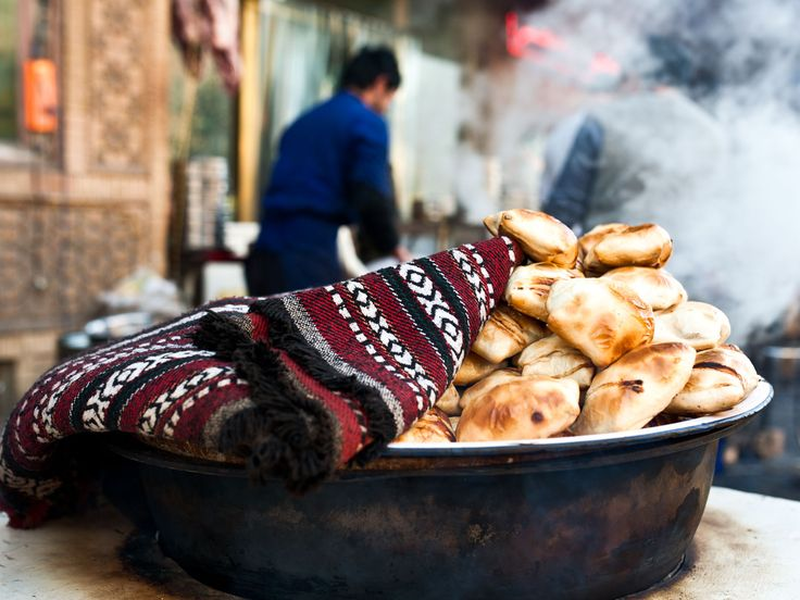 Samsas, unleavened pockets of wheat dough that are filled with mutton, folded over like envelopes, and then baked in a deep outdoor pit oven called a tanur. #food #Travel
