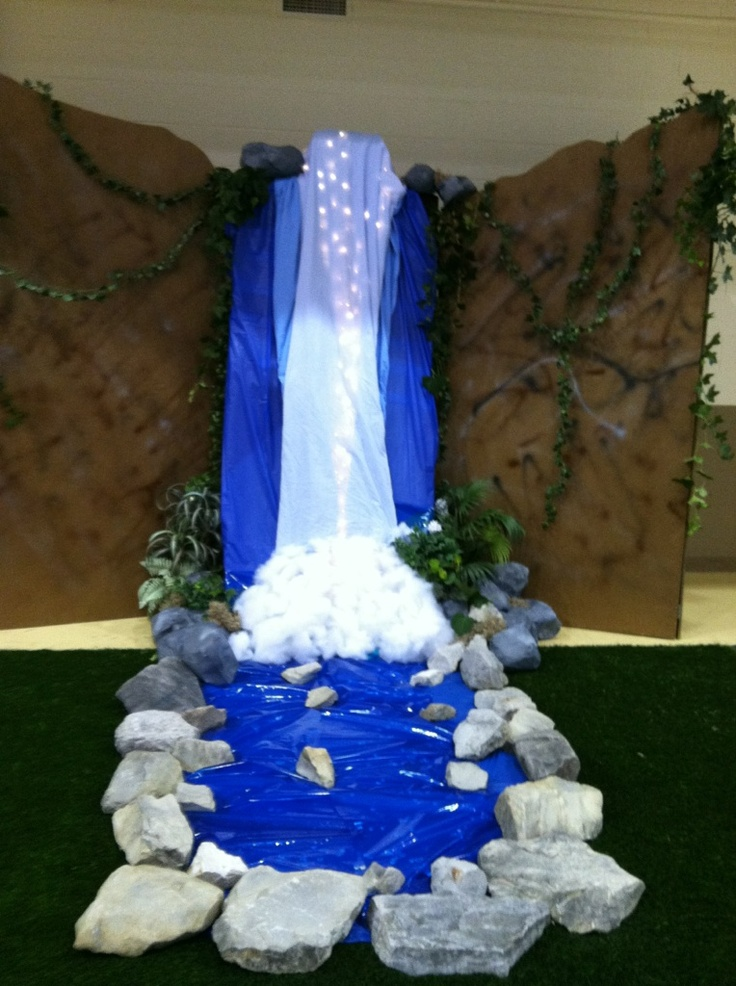 Waterfall for VBS. Made with wood backdrop, multiple blue colored sheets, lights, cotton, rocks, and greenery.
