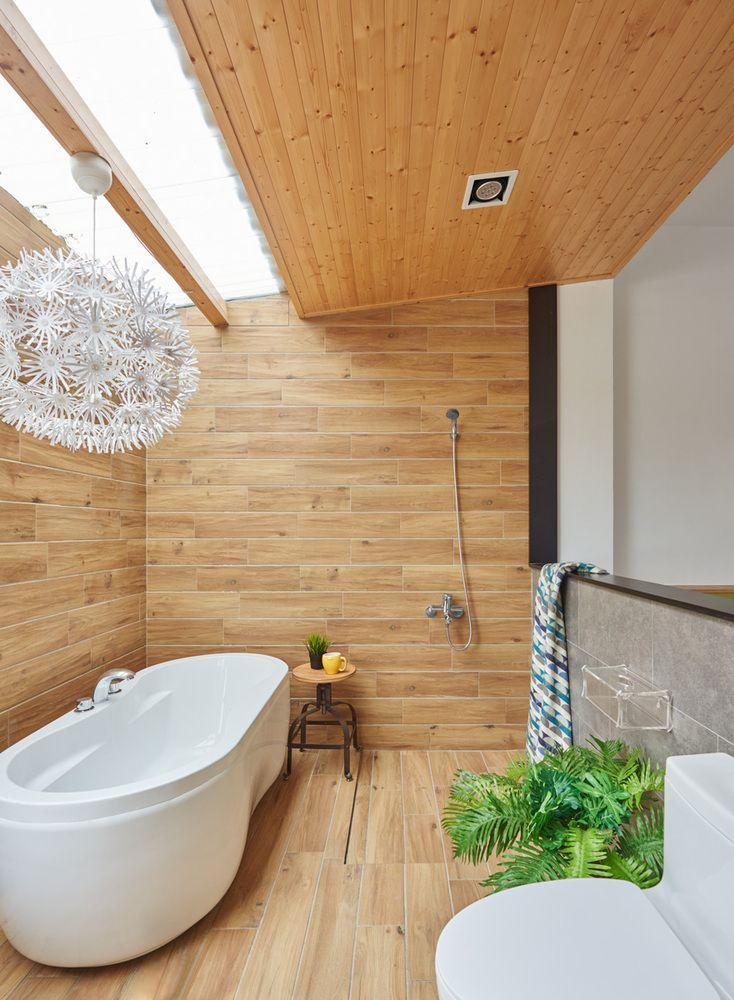 まるで屋外のように明るくて開放的な天窓と緑のある板張りのバスルーム