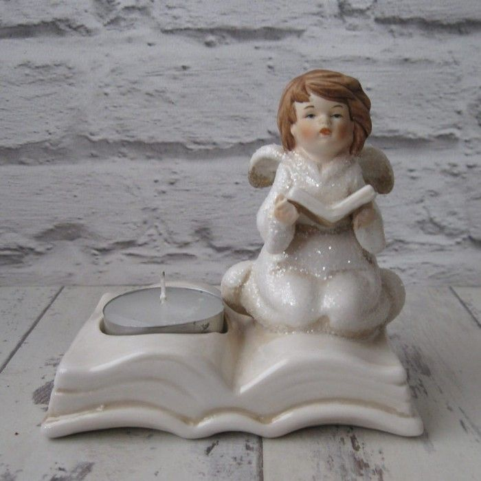 Porcelain Angel reading a hymn book tealight candle holder  This is a beautiful porcelain Angel tealight holder. The Angel is kneeling on a porcelain book while reading a hymn book. An insert is next to the Angel where a tealight candle can be placed.  The Angel reading a hymn book tealight candle holder is 12cms.