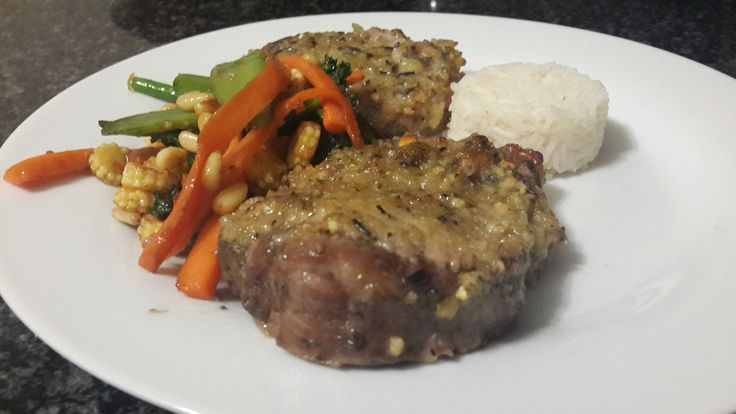 Pork chops topes with bread crumbs and herbs baked in oven for 40 minutes on a white wine and lemon sauce, served with vegetable sauted in butter, garlic and a sweet and sour sauce, and a side medalion of rice.