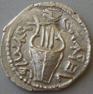 """Moedas em Qumran. A Zuz, era uma antiga moeda de prata judaica. A cunhagem de moedas da Revolta de Bar-Kochba foram moedas emitidas pelos judeus durante a revolta de Bar Kochba contra o Império Romano de 132-135 A.D. (a Terceira Revolta Judaica). Durante a revolta, grandes quantidades de moedas foram emitidas em prata e cobre com inscrições rebeldes. No anverso se viam trombetas cercadas por """"Para a liberdade de Jerusalém """". No reverso a lira cercada por """"Ano dois para a liberdade de Israel…"""