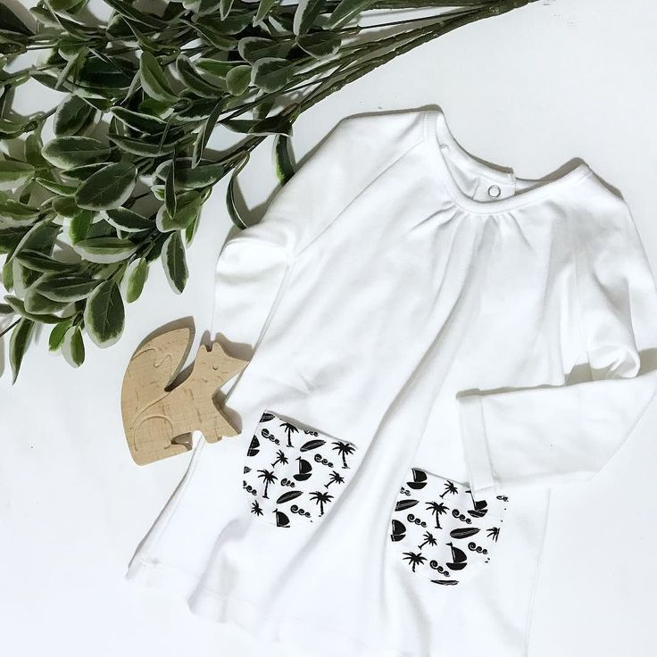 Happy Flat Lay Friday everyone What have you got planned for this beautiful spring weekend? . How good does our Ocean Child Organic Dress look pictured with the one and only Clever Fox Natural Beech Wood Teether Toy? . Simple natural organic goodness at its best . . . [image of a white long sleeve baby dress with black and white patterned pockets laid out on a white background alongside a fox shaped wooden teether toy and a branch of green and white leaves.