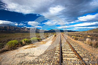 Railway line goes straight into the distance with the mountains with coming rain clouds at days end on the left hand side of the photo image. Low angle horizontal photograph captured on the rail track with the stones and supports along with the low fine bush vegetation. Coming rain clouds with afternoon blue sky giving contrasts to the moment.
