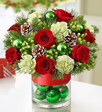 Glorious Christmas™ - #roses and carnations mixed with festive hypericum and evergreens, gathered in a glass vase filled with shimmering #ornament balls and pinecones.