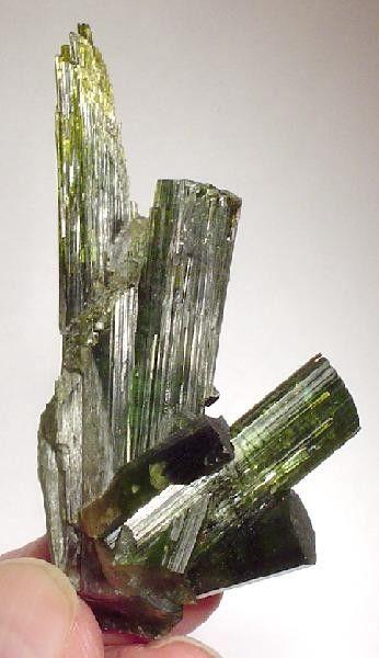 Elbaite da Mina Golconda, em Governador Valadares, vale do Rio Doce, Minas Gerais, Brasil. Um multi-eixo dramático, de  turmalina. Os brilhantes cristais verdes têm belos destaques amarelos e todos os grandes cristais são intocados. O longo cristal é esculpido, como é o outro cristal basal.  Fotografia: Rob Lavinsky.