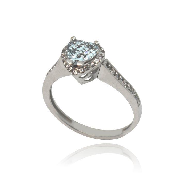 Mονόπετρο δαχτυλίδι, λευκόχρυσο 14 Καρατίων, διακοσμημένο με μία γαλάζια κεντρική πέτρα topaz Swarovski σε σχήμα καρδιάς και μικρότερες λευκές πέτρες σε ένα κομψό σχεδιασμό.