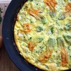A light and healthy frittata is perfect for breakfast or dinner. Using farm fresh eggs to show off delicate squash blossoms, it is delicious.